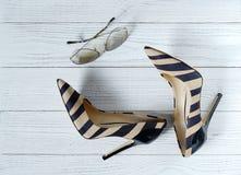 Women& x27; s鞋子和太阳镜在白色木背景 库存图片