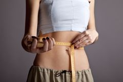 Women's abs with metre nad burger. Royalty Free Stock Images