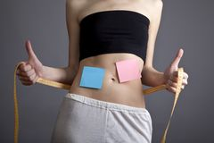 Women's abs with metre and note. Stock Image