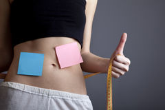 Women's abs with metre and note. Royalty Free Stock Photography