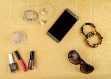Women`s accessories for a beach holiday. A smartphone with a blank screen, jewelry and cosmetics, sun glasses, headphones and a sh. Ell in the background of a stock photography
