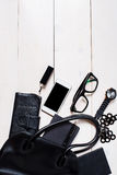 Women's accessories fell out of the black handbag on white background. Stock Photos