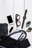 Women's accessories fell out of the black handbag on white background. Flat lay, top view, mock up women's accessories fell out of the black handbag on white Stock Photo