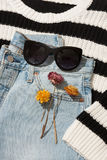 Women`s accessories and flowers. Female sunglasses lying on jeans near the flowers Royalty Free Stock Image