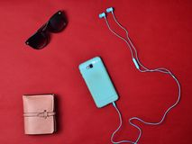 Women& x27;s accessories are lined on a red background. Smartphone, headphones, wallet, sunglasses. Flat lay.  stock images