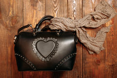 Women's accessory.  leather bag and scarf. New stylish women's leather bag decorated with a scarf. View from above. One bag on a wooden background Stock Photo