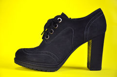 Women's ankle boots in black suede on a yellow Stock Image
