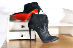 Women`s Ankle boots handmade. Imitation brand shoes Christian Louboutin, showing red soles Stock Photo