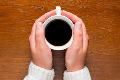 Women's arms wrapped around a hot cup of coffee Royalty Free Stock Photo