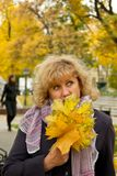 Women's autumn. Portrait of a middle-aged attractive woman with yellow autumn leaves Royalty Free Stock Photos
