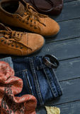 Women's autumn clothing and accessories - boots, jeans, scarf, bag, on dark wood surfaces Stock Image