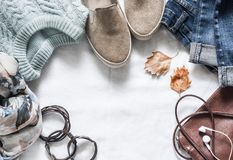 Women`s autumn clothing set - jeans, suede sneakers, pullover, scarf and leather bag. Women`s clothes for autumn walks on a ligh Stock Photography