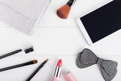 Women`s bag, lipstick, hair clip, phone. Flat lay female composition. Women`s cosmetics and phone stock images