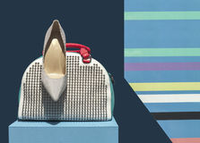 Women's Bag and Shoe on Display. Women's white studded handbag with red handle and striped shoe on a display stock image