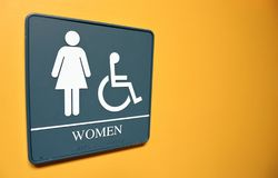 Women`s bathroom sign on orange wall with space for text and handicapped symbol stock photo