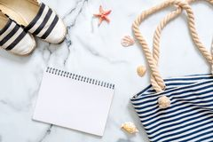 Women`s beach accessories and blank notepad on marble background, summer holidays journey concept. Summer beach set: striped sand stock images