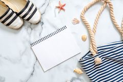 Women`s beach accessories and blank notepad on marble background, summer holidays journey concept. Summer beach set: striped sand royalty free stock image