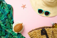 Women`s beach accessories, straw hat, beach bag, sunglasses, coconut on pink background with copy space for text. Travel vacation royalty free stock photography