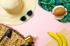 Women`s beach accessories: straw hat, sunglasses, banana, coconut, beach bag with essential oil on pink background. Travel concep stock photo