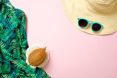 Women`s beach accessories, straw hat, sunglasses, coconut on pink background with empty space for text. Travel vacation concept. royalty free stock photography