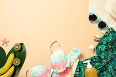 Women`s beach accessories: straw hat, sunglasses, swimwear, green scarf, suntan lotion, banana on yellow background. Travel royalty free stock image