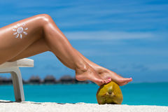 Women's beautiful legs on coconut on the beach, blue sea backgro Royalty Free Stock Images