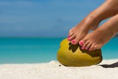 Women's beautiful legs on coconut on the beach, blue sea backgro Stock Photo