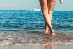 Women`s beautiful sexy legs on the beach royalty free stock images