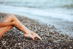 Women`s beautiful legs on the beach. Summer time stock photography