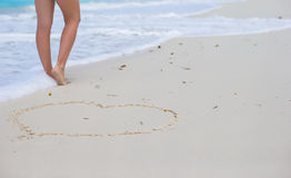 Women's beautiful smooth legs standing near big heart on white sand beach Stock Photography