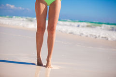 Women's beautiful smooth legs on white sand beach Stock Photography