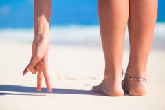 Women's beautiful smooth legs on white sand beach. See my other works in portfolio Royalty Free Stock Photos