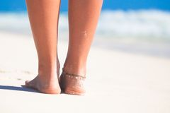 Women's beautiful smooth legs on white sand beach Stock Photo