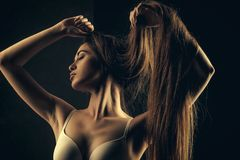 Women`s beauty. woman with long healthy hair in underwear bra. On black background, hairdresser and beauty salon royalty free stock photos