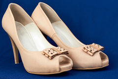 Women's  beige leather   peep-toe shoes with bow. On a blue  background Royalty Free Stock Image