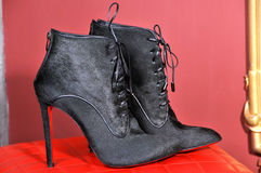 Women`s black fur, ankle boots handmade. Imitation brand shoes Stock Photos