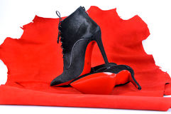 Women`s boots handmade on a piece of material from the red skin. Imitation brand shoes Stock Photo