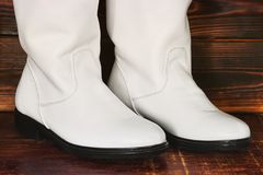 Women`s boots on wooden background. White skin royalty free stock images