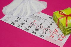 Women`s calendar on which are hygienic and daily pads, pink background, copy space, intimate royalty free stock images