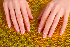 Women's care and beauty. Stylish moon french manicure on a golden background. Women's care and beauty royalty free stock images