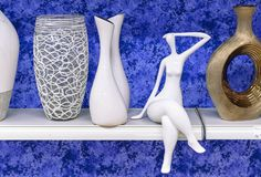 Women`s ceramic statuette on a shelf with vases stock photo