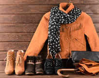 Women's clothing and accessories. Brown suede jacket, three diff. Erent pairs of shoes, scarf, umbrella and black leather bag Stock Image