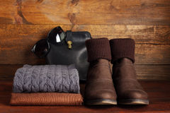 Women's clothing and accessories. Glasses, scarf,sweater, bag, shoes, bright wooden surface Stock Images