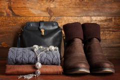 Women's clothing and accessories. Jewelry, scarf,sweater, bag, shoes, bright wooden surface Royalty Free Stock Image