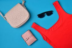 Women& x27;s clothing and accessories laid out on a blue background. Red T-shirt, purse, bag, sunglasses Top View. Flat lay. Women& x27;s clothing and stock image