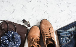 Women's clothing and accessories - suede boots, jeans, leather bag, scarf. On a light background. Top view stock photos
