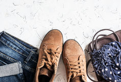 Women's clothing and accessories - suede boots, jeans, leather bag, scarf. On a light background. Top view stock image