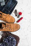 Women's clothing and accessories - suede boots, jeans, leather bag, scarf, red nail polish and lipstick. On a light background, top view royalty free stock image
