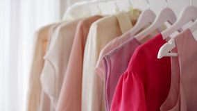 Women`s clothing blouses in pink, beige and cream shades on a white hanger