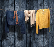 Women's clothing on a clothesline on wood background Stock Photos